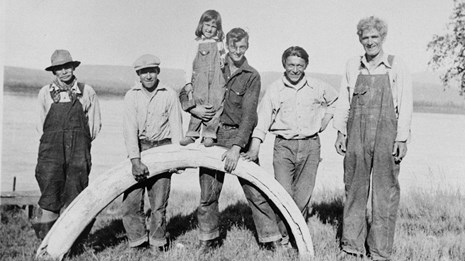 Historic photo of men standing on Yukon River shore with mammoth tusk