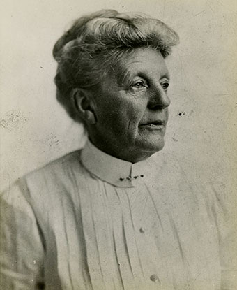 Black and white photo of an older woman, hair in a bun, pleated white shirt pinned at the collar.