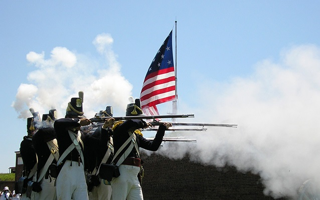 Soldiers fire their weapons in Fort McHenry reenactment