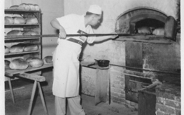 man taking bread out of the oven at Hahn's bakery