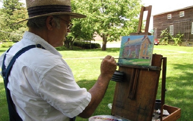 man painting outside the amana arts guild