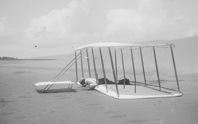 Wilbur laying prone on glider just after landing, skid marks visible on right- Kitty Hawk, 1901