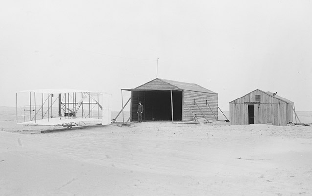 1903 Wright Flyer parked to the left of two camp buildings- Kitty Hawk, 1903