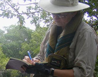 woman writing outdoors in a journal