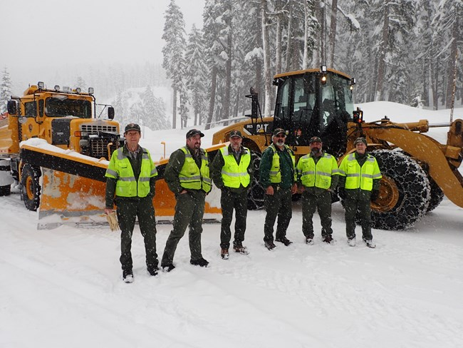 Six men in bright yellow safety vests stand in front of two big snow plows.