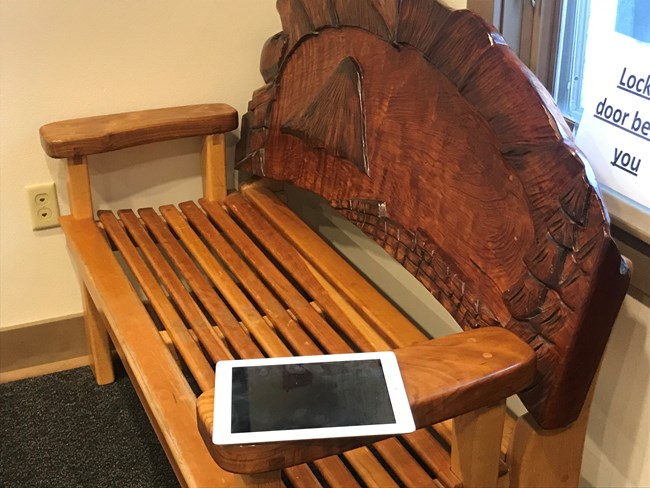 I-pad sitting on wooden bench left by unknown owner.