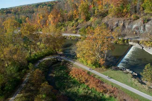 The Brecksville lowhead dam viewed from above, surrounded by fall colors.