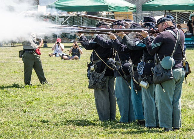 Union soldiers fire their rifles during a living history demonstration.