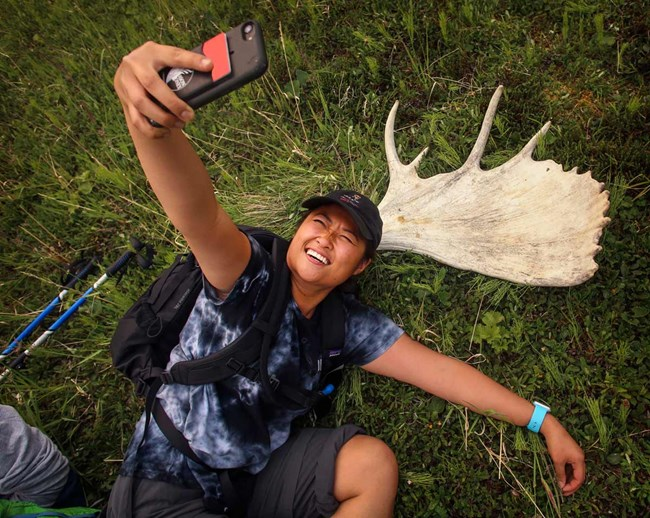 a woman laying on the ground taking a selfie next to a moose skull
