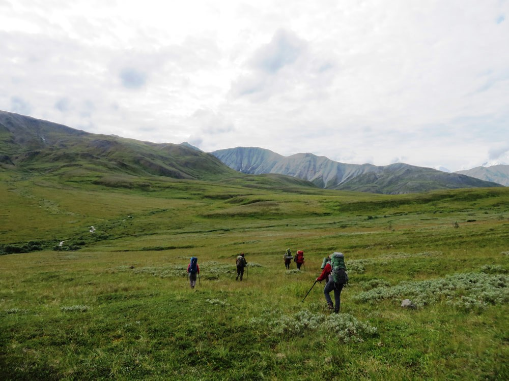 a group of people hiking through a tree-less landscape of hills and mountains