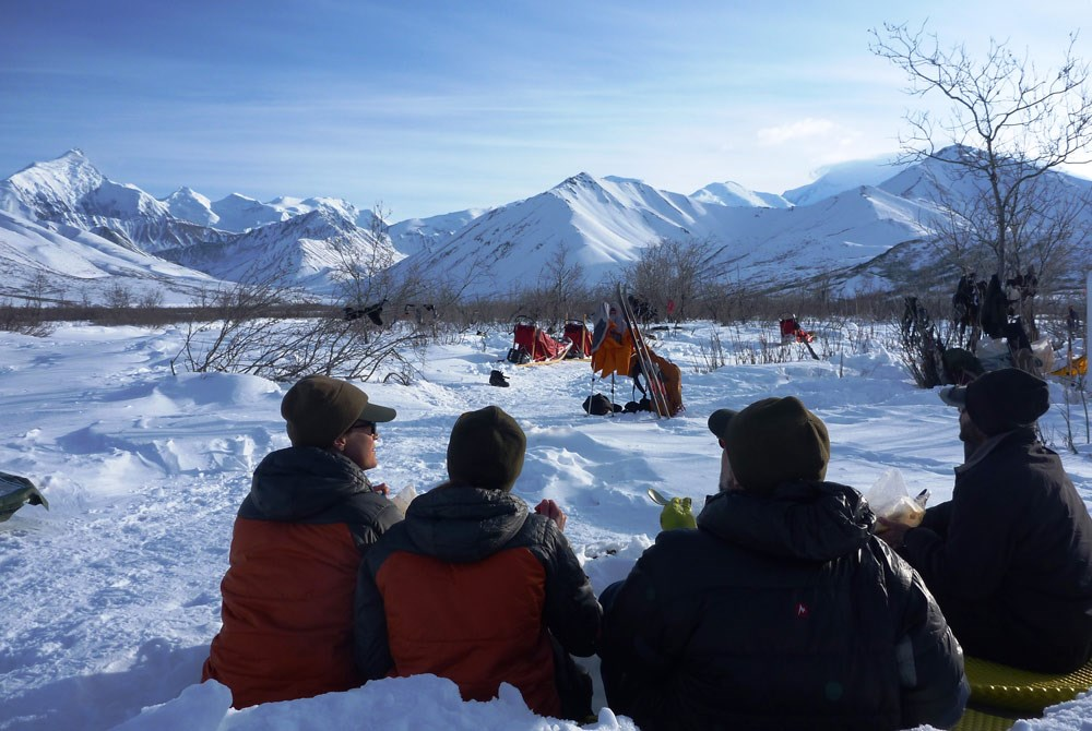 people in winter attire sitting on the snow, looking at a nearby tent and distant, snowy mountains