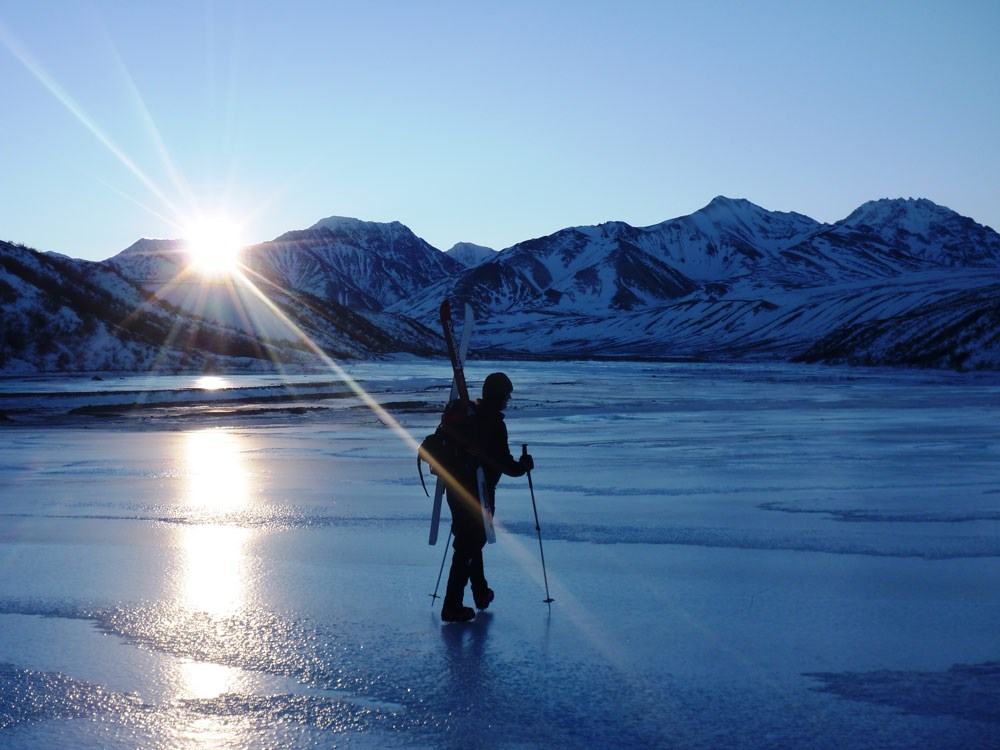 a person with skis strapped on her back walks across a frozen, icy river or lake