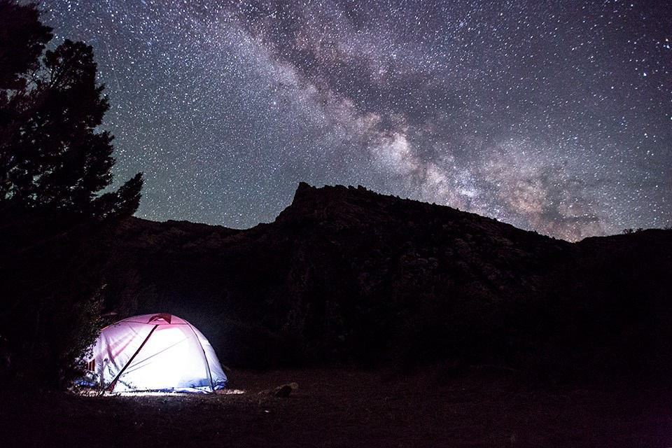 Lighted tent underneath a starry sky