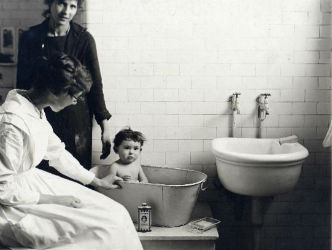 Ellis Island nurse Lillian Wheeler giving a child a bath.