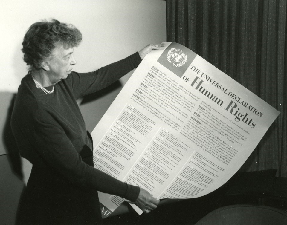 A woman holds a large printed version of the Universal Declaration of Human Rights.