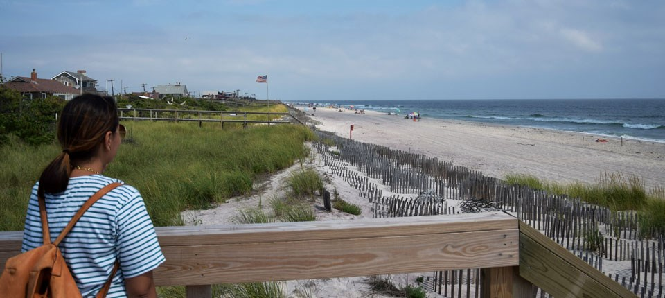 Visitor overlooks dunes, beach, and ocean from boardwalk.