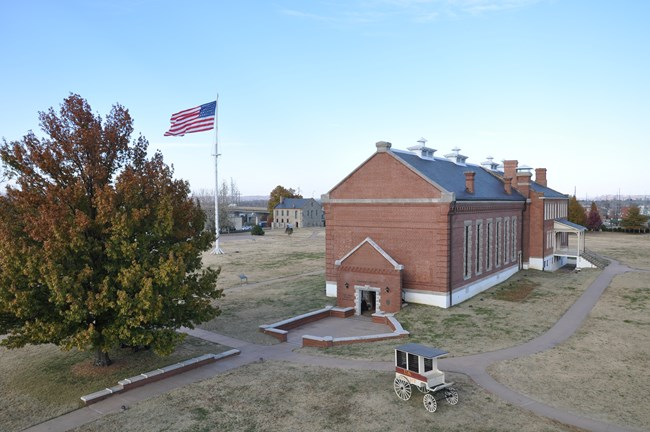 Aerial view visitor center entrance, jail wagon, garrison flag flying over the parade ground, and commissary in background