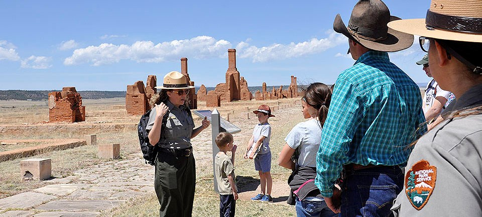 Female ranger speaking to visitors in front of adobe ruins