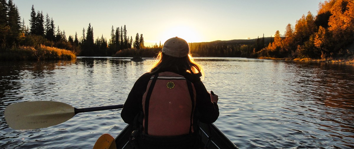 Woman paddling a canoe towards sunset on a forested river