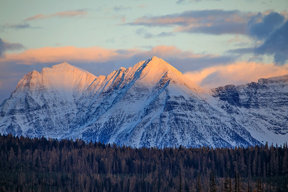 The setting sun highlights the new snow on the peaks in the North Fork