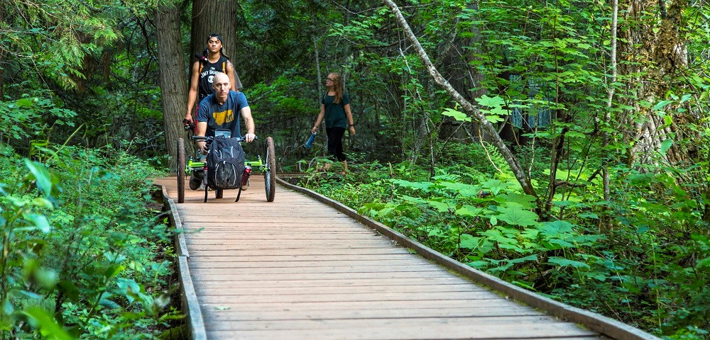 man with off-road wheelchair followed by visitors walking on boardwalk trail