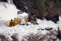 A snow plow and an excavator remove snow from a cliffy section of the Going-to-the-Sun Road.