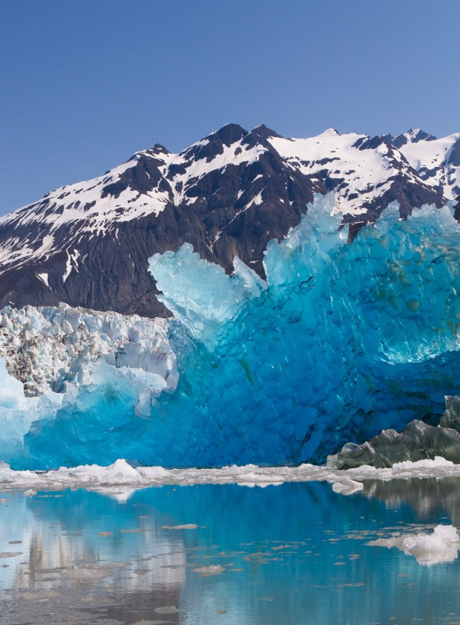 Rocky, snowy peaks frame the background of a water scene highlighted by a huge jagged chunk of electric blue ice, with a glacier visible behind it.