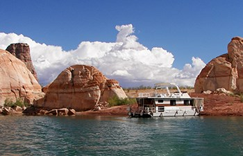Houseboat on lakeshore with red rock formations and growing clouds in background