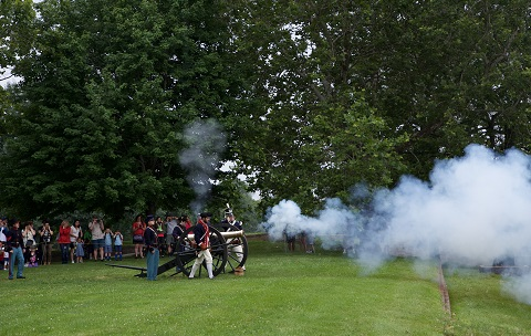 Cannon firing in front of Fort Jay