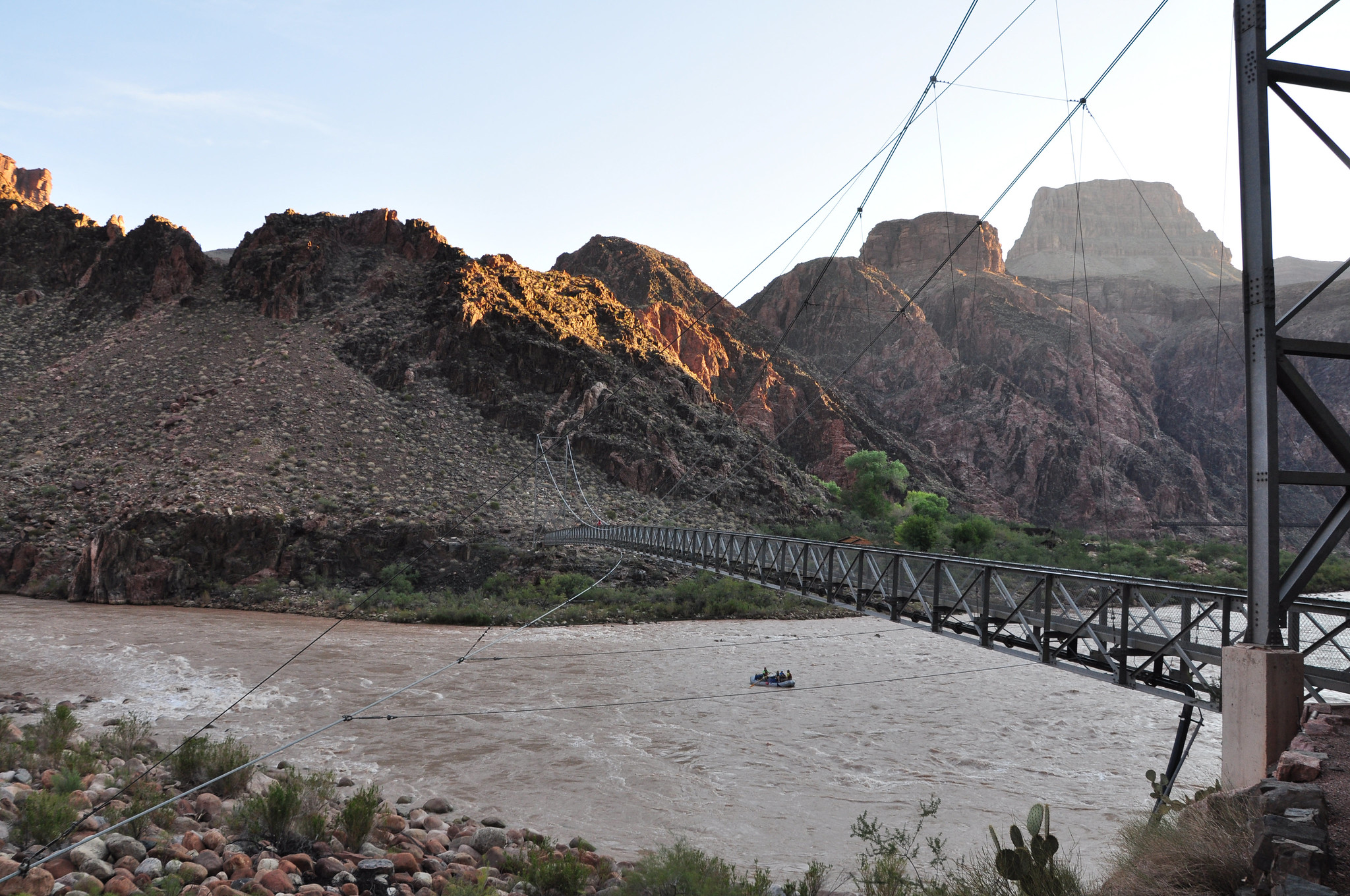 Boaters on the Colorado River pass under the Silver Bridge while getting an early start on their day's journey. NPS Photo by Erin Whittaker.
