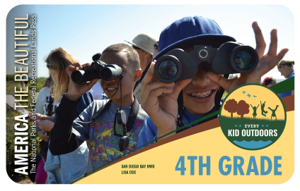 2020-2021 Every Kid Outdoors 4th Grade Pass shows a group of youth and adults outside. Two youth in the foreground are looking directly ahead and to the right through binoculars.