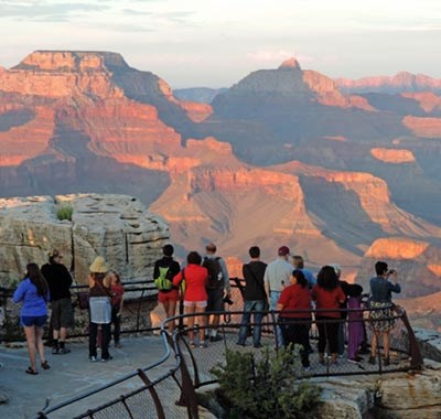 Vermilion sunset light on buttes and peaks within Grand Canyon. A number of people are watching the sunset from behind a metal guardrail