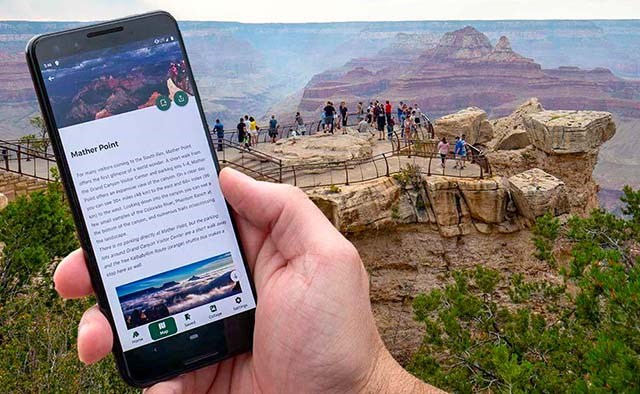 a hand holding cellular phone that displays photos and text for a location. In the background, people at a scenic overlook with peak visible in the distance