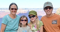 family of 4 with 2 girls in between parents, grand canyon in background