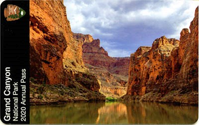 Front of Grand Canyon National Park 2020 Annual Pass shows a clam and green Colorado River beneath sheer cliffs that rise from the river's edge.