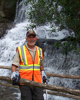 A volunteer stands in front of a waterfall