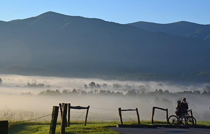 Bicyclists in Cades Cove pause along the road. Behind them mountains rise up from a foggy valley.