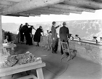 Naturalist Edwin McKeee shows the canyon to visitors from the parapet of Yavapai Observation Station. Circa 1930. NPS Photo
