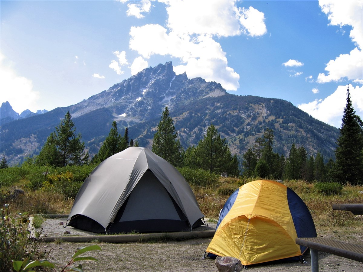Two tents in a campground in front of a mountain.