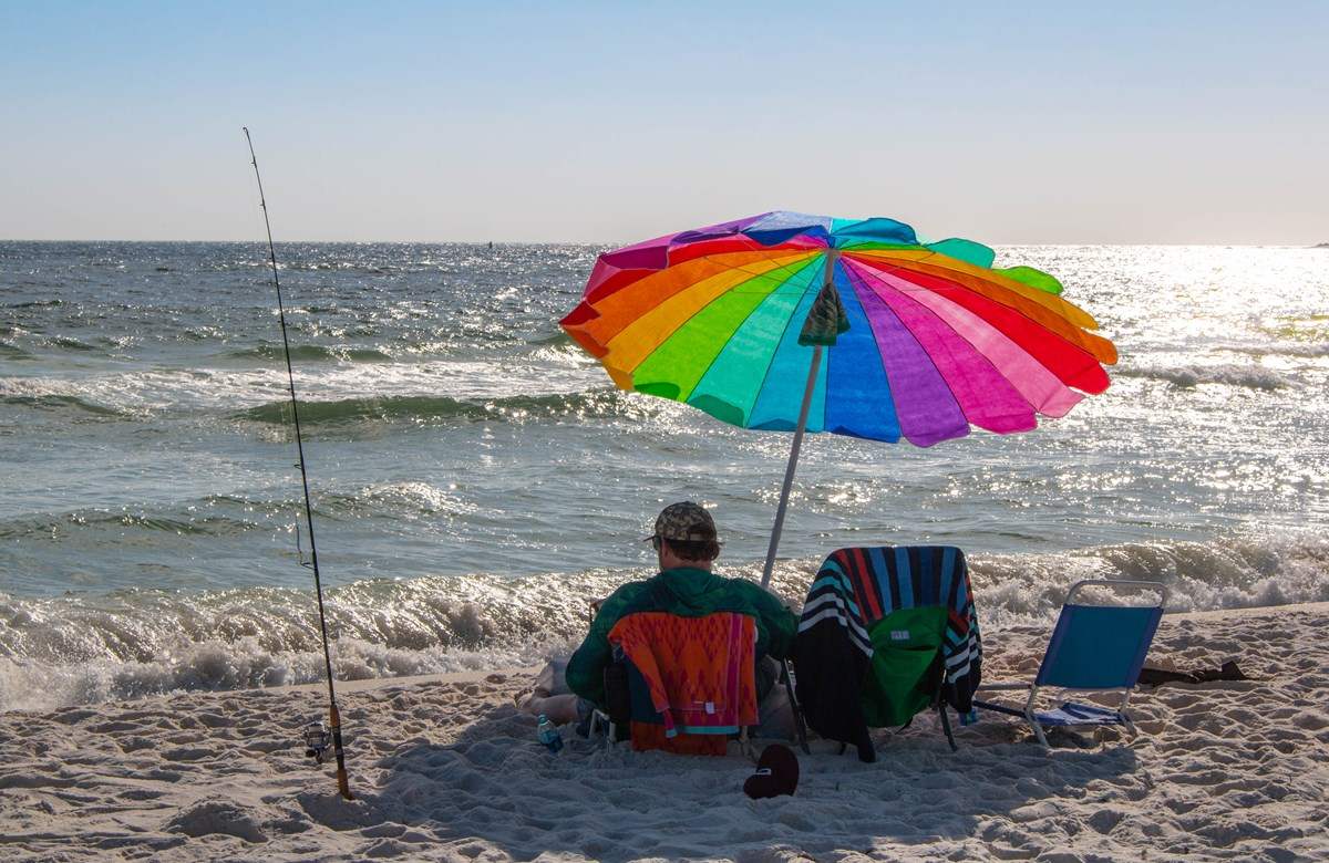A man sits under a rainbow umbrella with a fishing pole in the sand to his left and the ocean in the background.