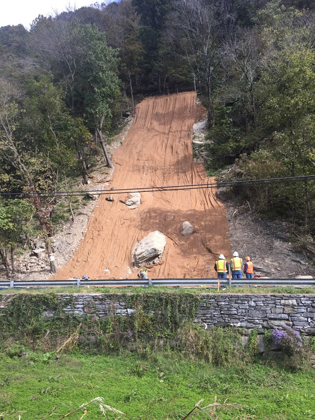 landslide area covered in mesh; construction workers stand nearby