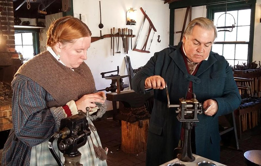 Volunteers practicing the art of tinsmithing
