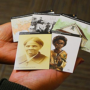 Historical trading cards fanned out in a woman's hands
