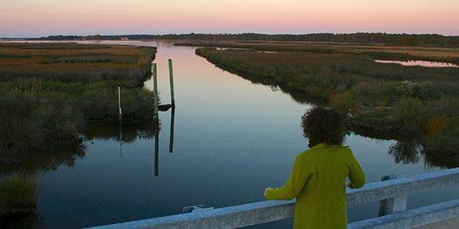 Sunset along Stewart's Canal, with a woman standing on a bridge overlooking the straight corridor of water with pink and purple skies