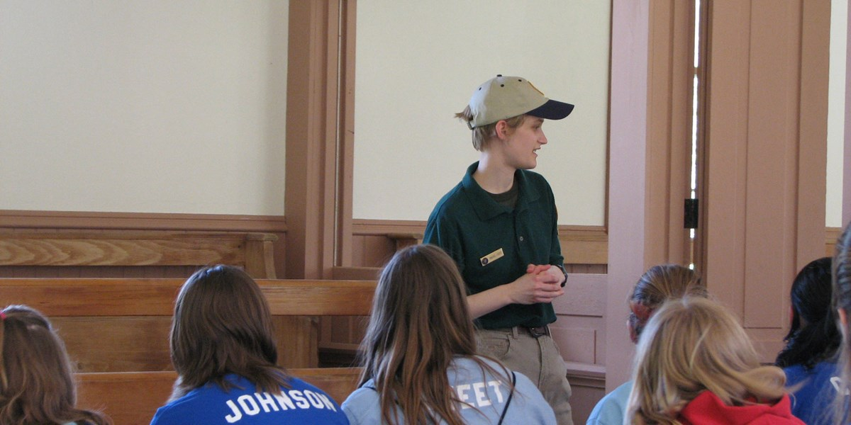 A woman in a volunteer uniform speaks to schoolchildren in a historic building.