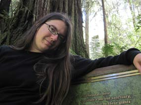 A woman sits by a commemorative plaque among redwood trees.