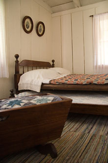 A bed and cradle furnish a small bedroom.