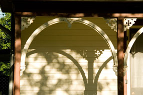 Wooden ornamental arches cast a shadow on the side of a historic house.
