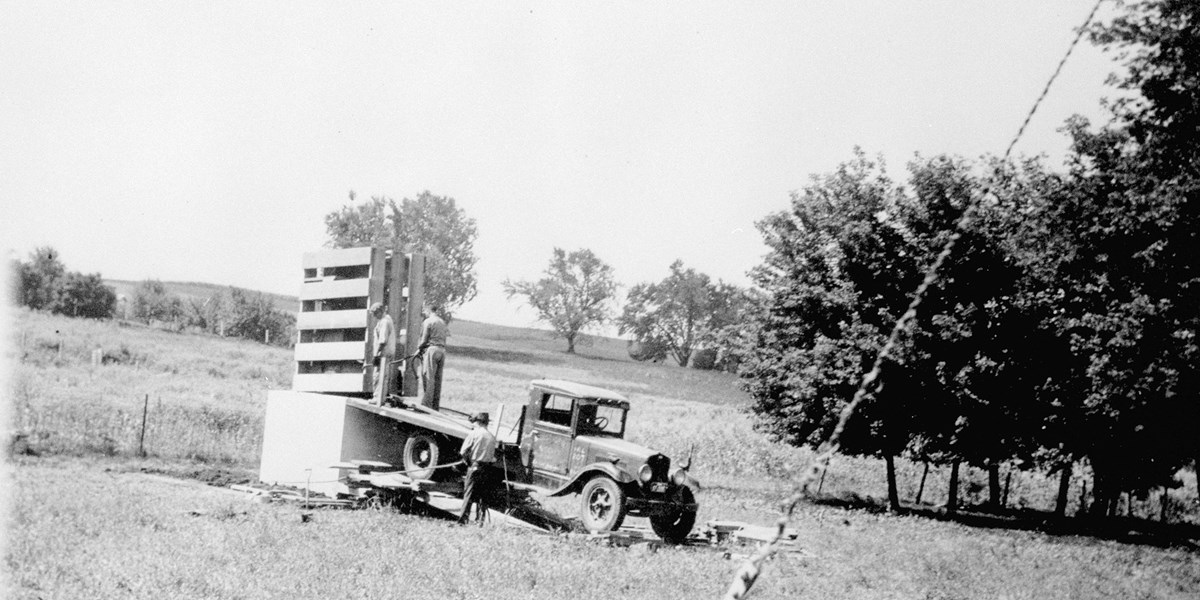 Workmen move a crated statue from a 1930s model pickup truck to a concrete pedestal in a field.