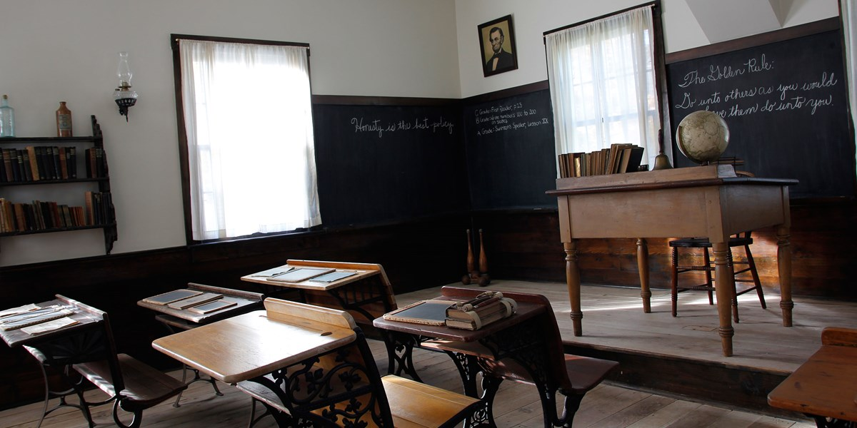 An 1870s classroom displays wood and iron pupils' desks in rows and a teacher's desk on a raised platform.